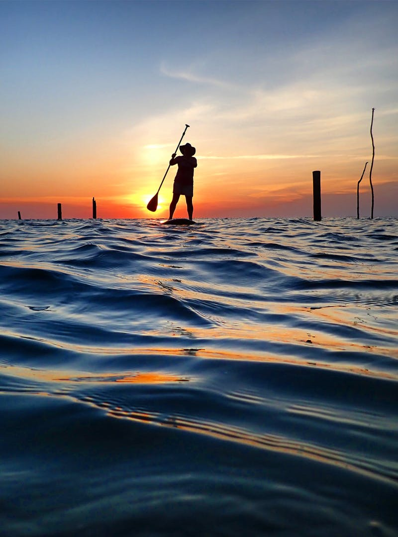 The silhouette of a person stand-up paddleboarding at dusk.