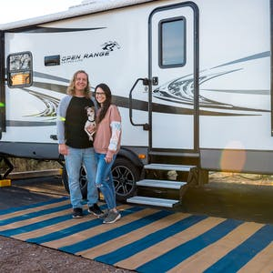 A young couple and their small doc stand outside their Heartland Open Range RV posing for a picture.