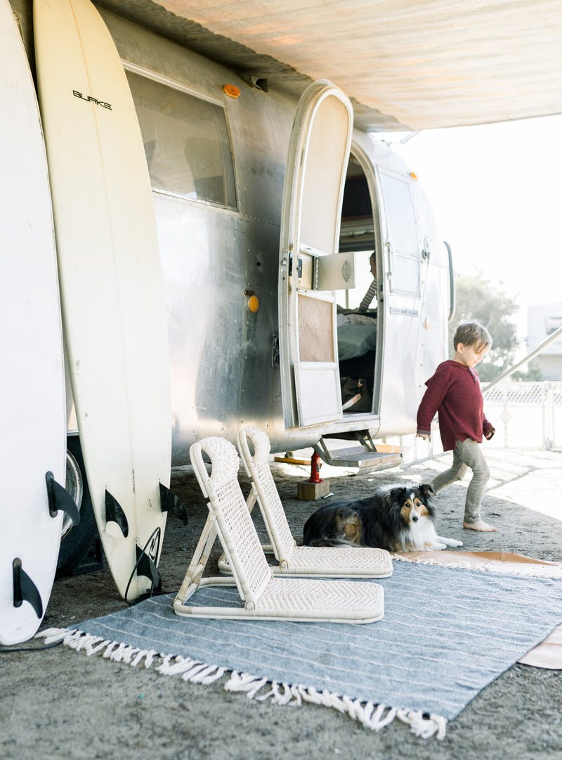 Child leaving through the front door of the Airstream RV, two surfboards rest against the side, with two beach chairs, and a mat on the ground.