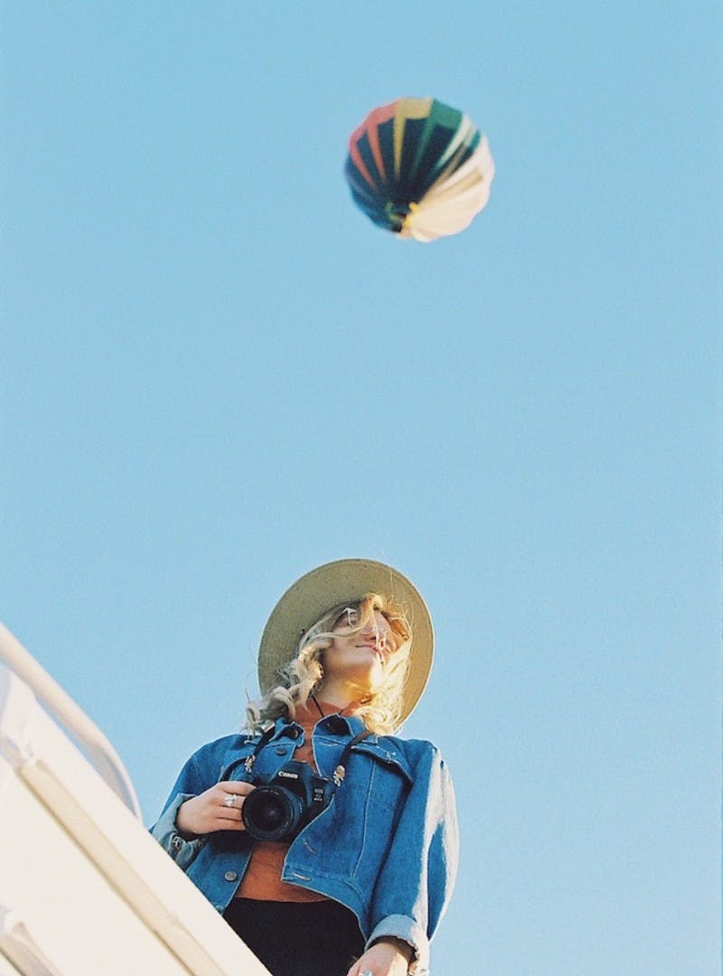 Image looking up at Natalie Allen on top of Entegra Class C RV with a hot air balloon in the sky.