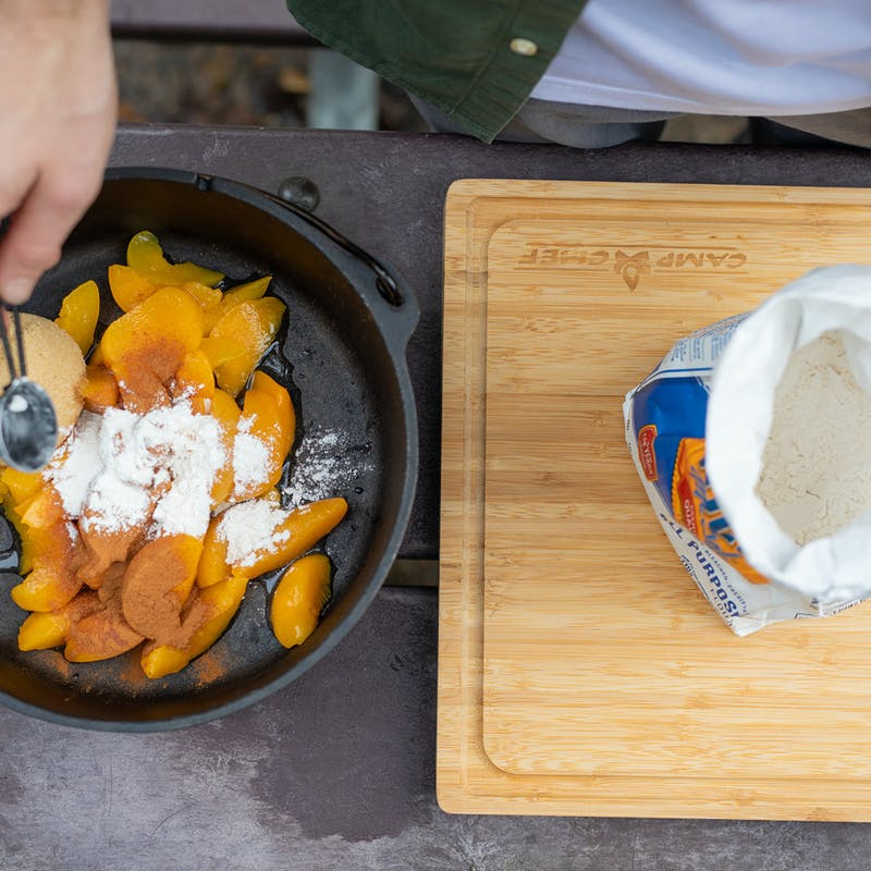 Sprinkling flour over peaches in a dutch oven with brown sugar and cinnamon.