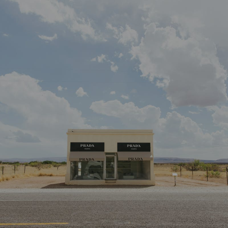 Prada Marfa building on a bright day against blue sky and clouds