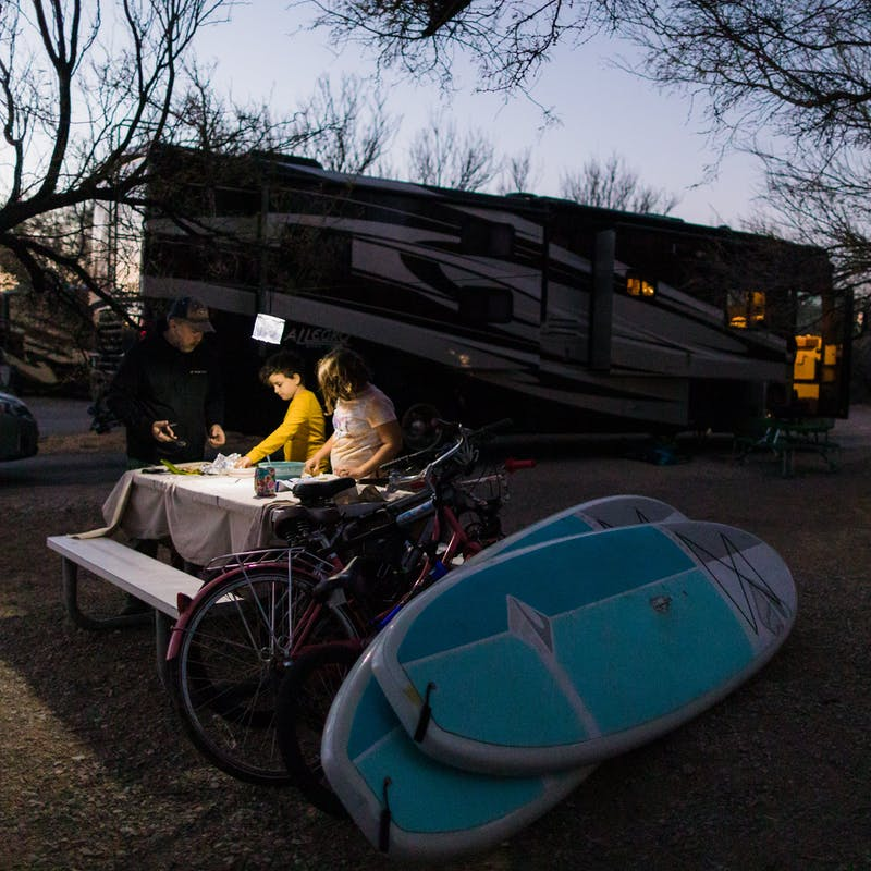 Desiree Walters children and husband set out dinner at dusk at a campsite with their Class A Allegro RV in the background.