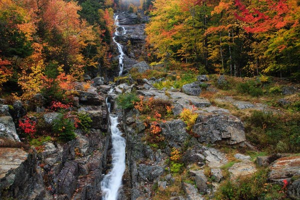 Waterfall surrounded by colorful fall trees and dark rocks