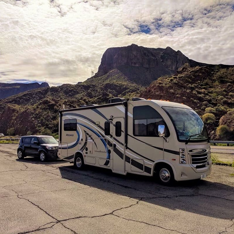 An RV towing a car, parked with a mountain in the background.