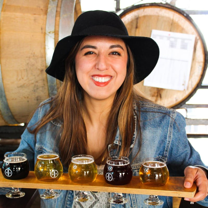 Rachael Lyons smiles holding up a beer flight.