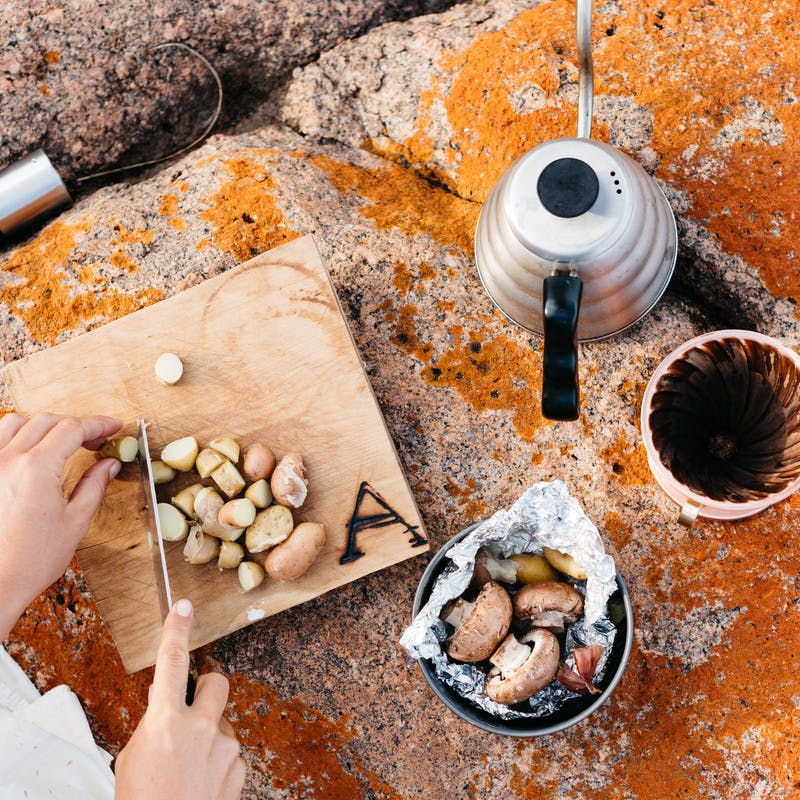 Cutting potatoes on a cutting board, with a bowl of mushrooms and fresh brewed coffee.
