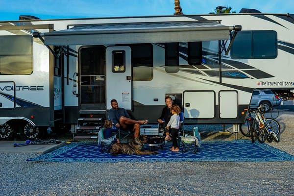 Samantha and Blake sit under the awning of their Dutchmen Voltage with two children.