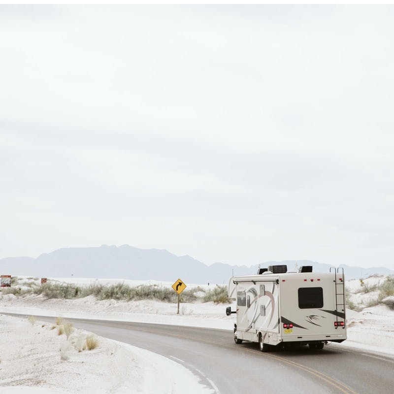 Class C motorhome drives on sandy road through White Sands National Park in New Mexico.