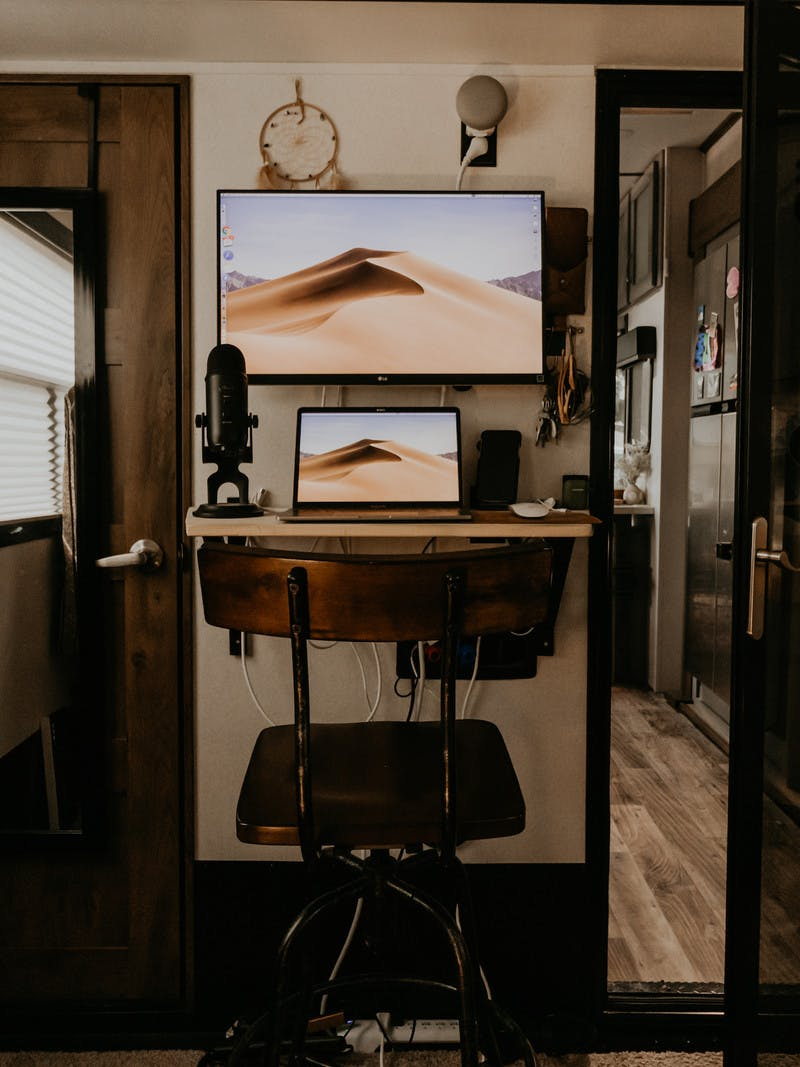 A laptop and a bigger screen set up at a narrow, but efficient work desk inside an RV bedroom.