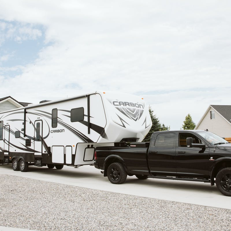 Exterior shot of a truck hitching a toy hauler RV in the driveway of Steve and Suzanne Talbot's home.