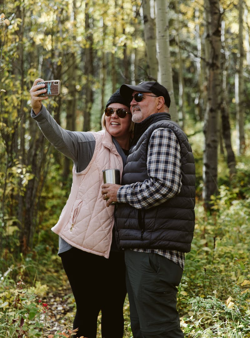 Tina and Craig standing in the woods, smiling and taking a selfie together.