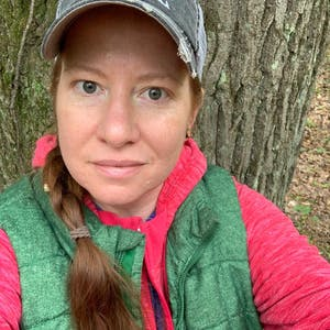 A selfie of Amy Lundquist-Stachowiak sitting in front of a tree wearing a hat and green vest