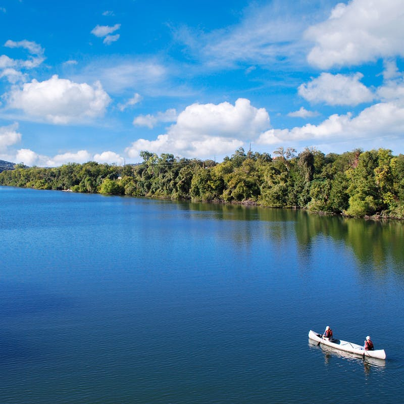 Two people canoeing on the placid blue waters of Lady Bird Lake.