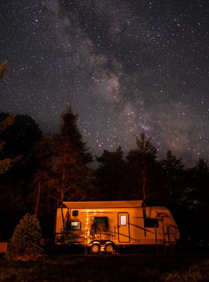 Exterior shot of a Jayco travel trailer RV at night under a starry night.
