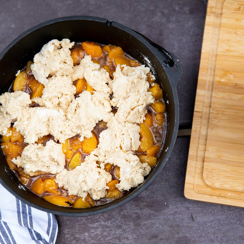 Peach cobbler assembled in a dutch oven and ready to bake.