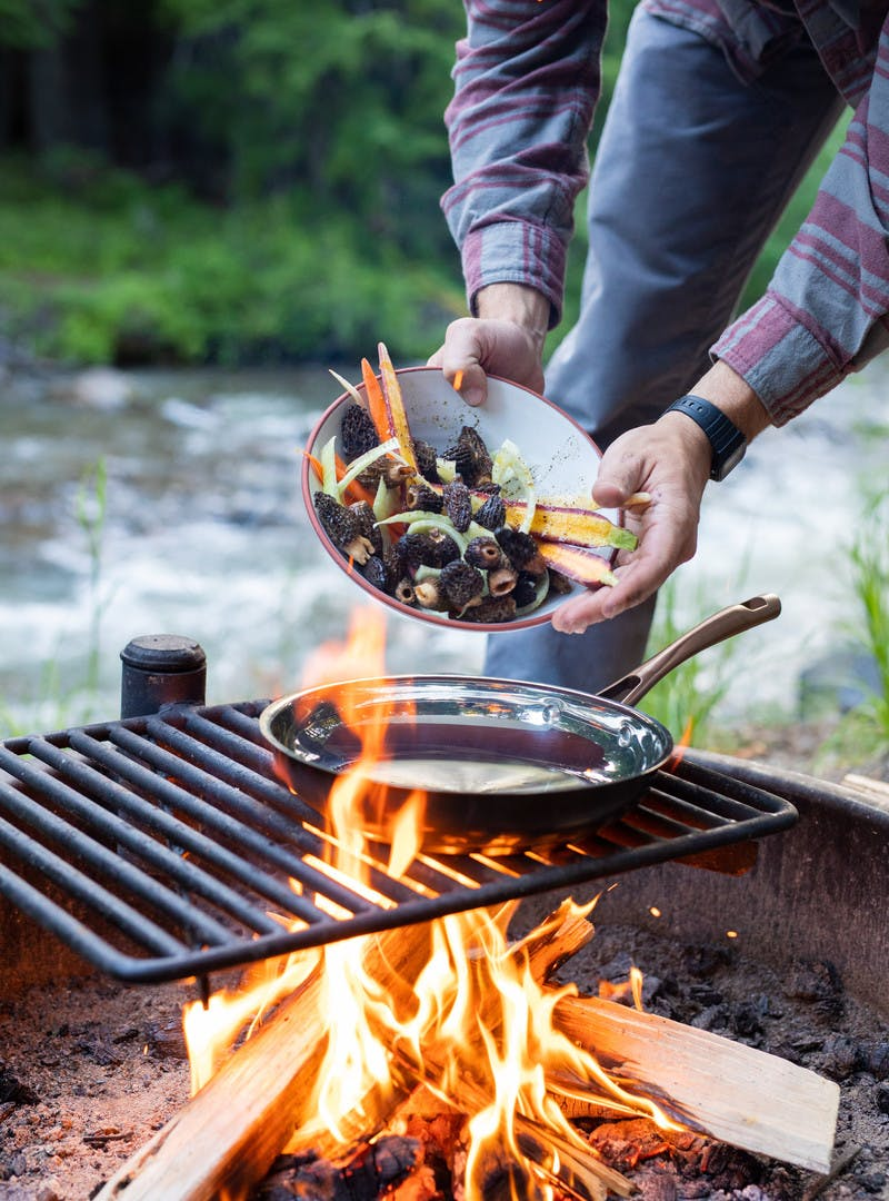 Man in flannel drops bowl of carrots, morels and fennel into frying pan over campfire.