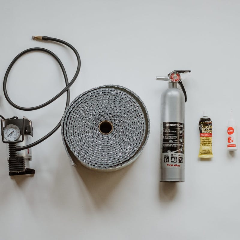 Shot of various RV essential items, including tire pressure gauge, fire extinguisher, glue and tape