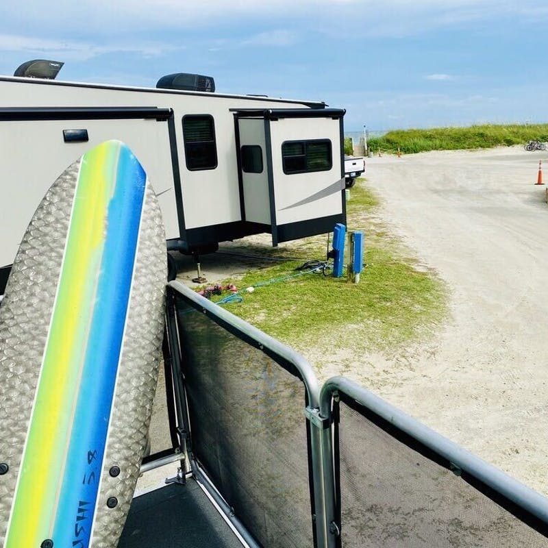 Eric Hannan's RV parked in a sandy campsite.