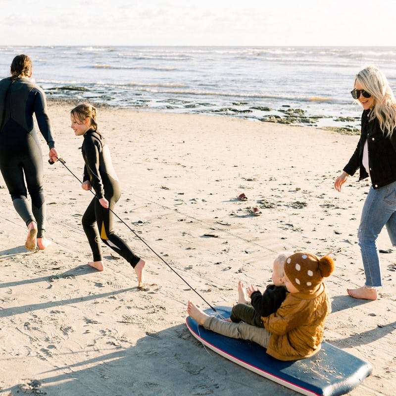Amber Thrane and her family playing on the beach and pulling a sled with their kids on it.
