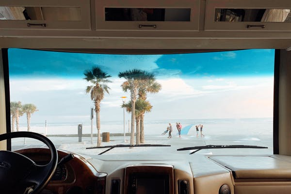 View out front windshield of palm trees, ocean, waves, and family playing in Gulf Shores, Alabama