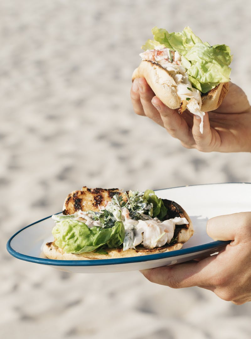 A hand holding an assembled lobster roll as well as another hand holding a plate with another lobster roll on it.