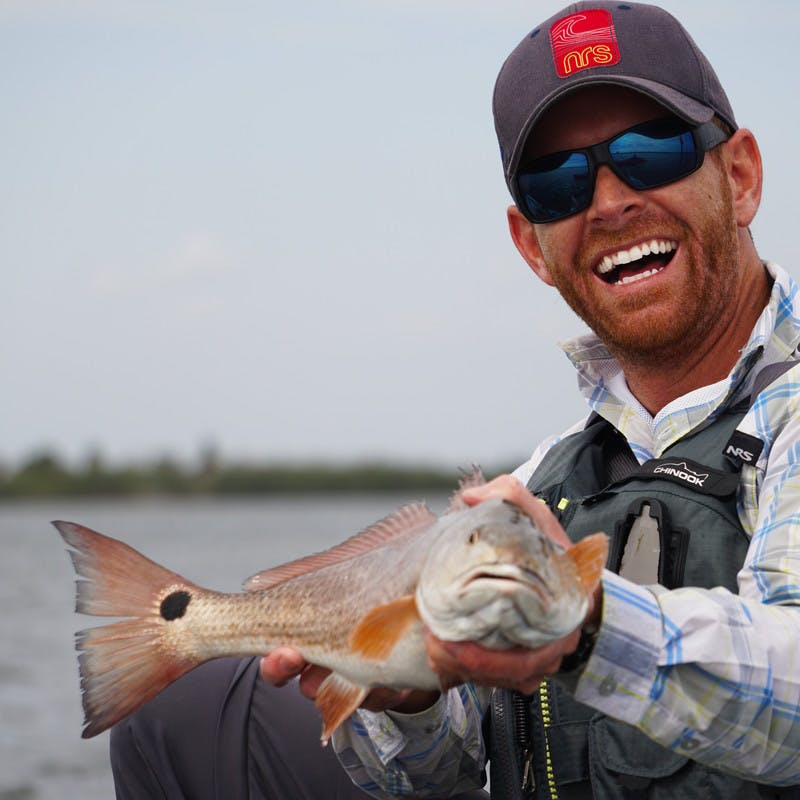 Robert holding up a redfish and smiling at the camera.