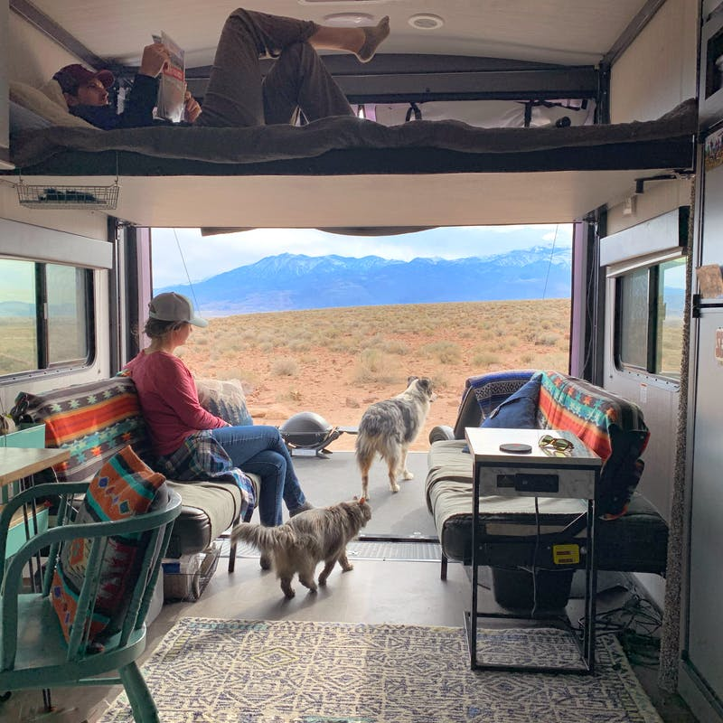 Amy Rekart looks out the back of her Cruiser Stryker toy hauler while her husband reads on the above bunk.
