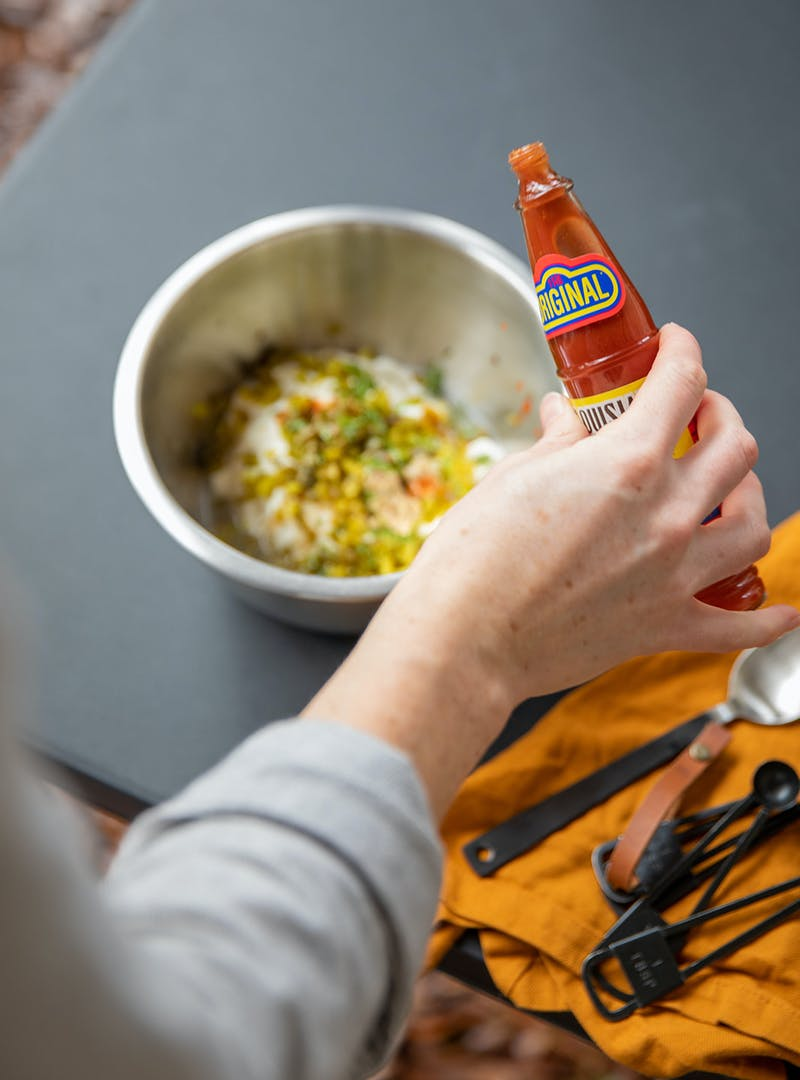Adding hot sauce to remoulade ingredients.