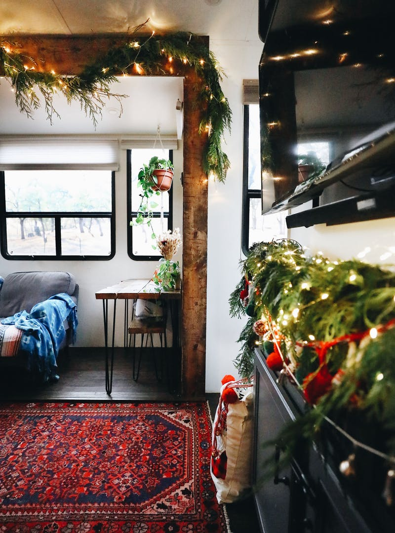 A living area in an RV decorated in pine boughs and Christmas lights.
