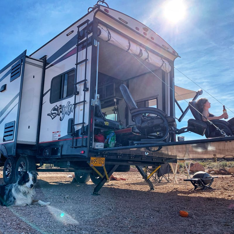 Amy Rekhart sunbathes and enjoys a beverage on the porch of her Cruiser Stryker toy hauler.