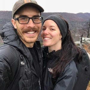 Jonathan Moore and Aubrey Janelle selfie, both wearing backpacks and waterproof jackets, with the mountains in the background.