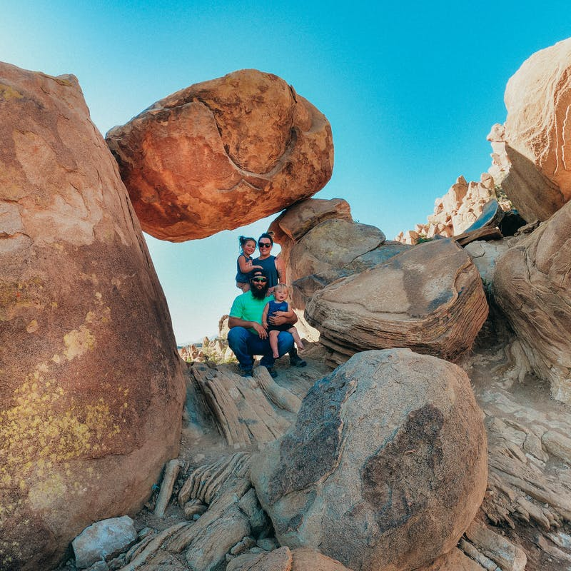 Sammy Seles' family poses on a hike through the desert with large rocks.