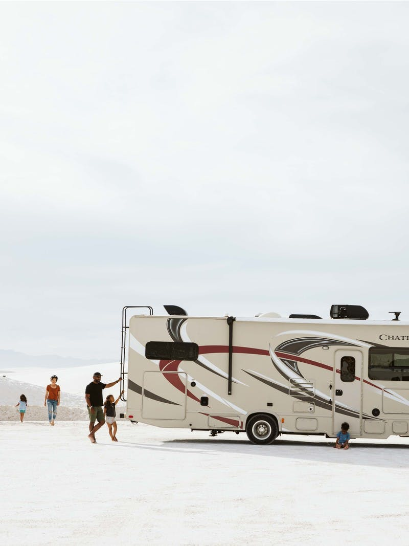 Family of four walking around large Class C motorhome at White Sands in New Mexico.