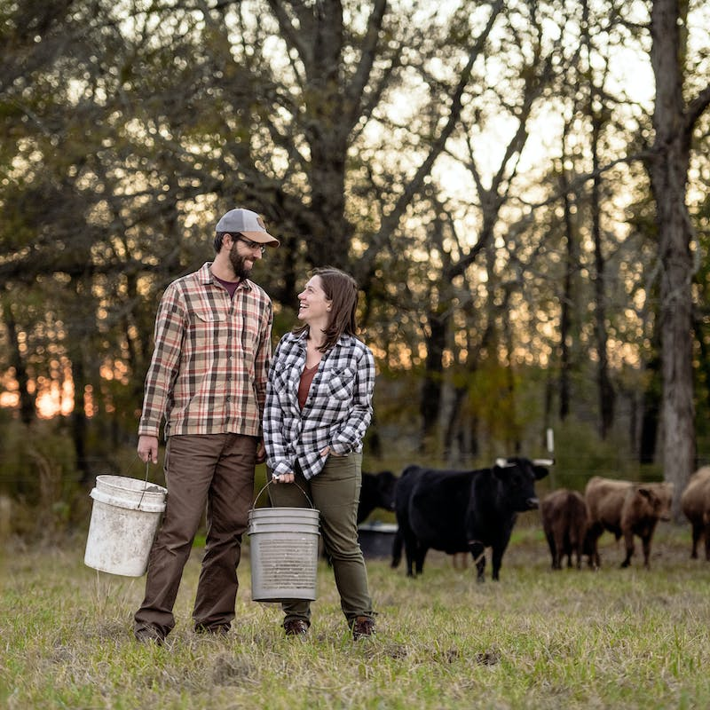 Todd & Marcia Schabel smile at each other holding buckets of crops on a farm.