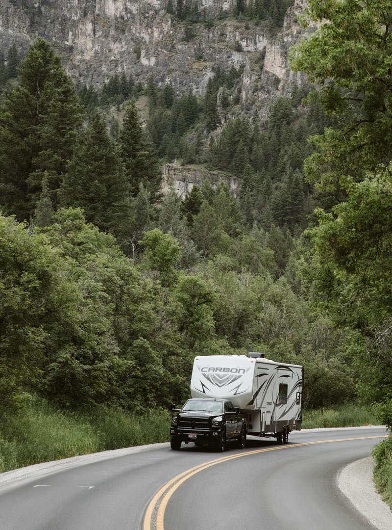 Driving shot of Toy Hauler RV being towed by a truck on the road with mountains in the back.