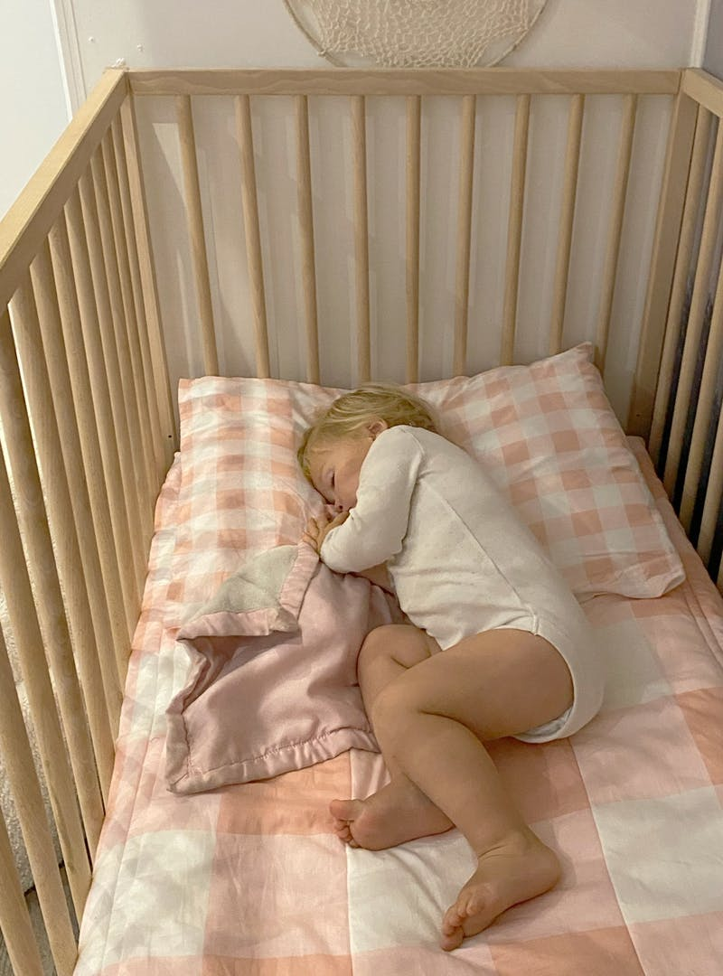 A young child asleep in a crib.