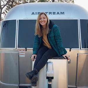 A photo of Stacey Powers sitting on her classic Airstream travel trailer RV.
