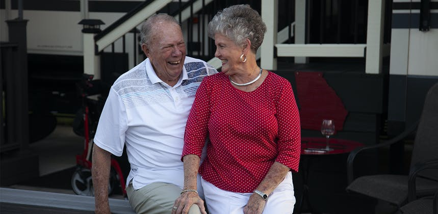 A senior man and woman laughing together as they are posed for a portrait.