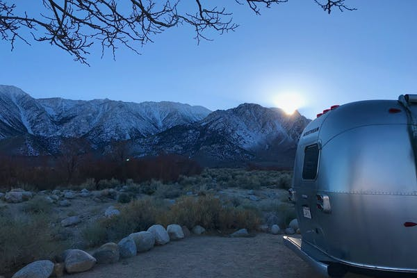 Dr. Na's Airstream parked at a campsite with snow capped mountains in the distance.