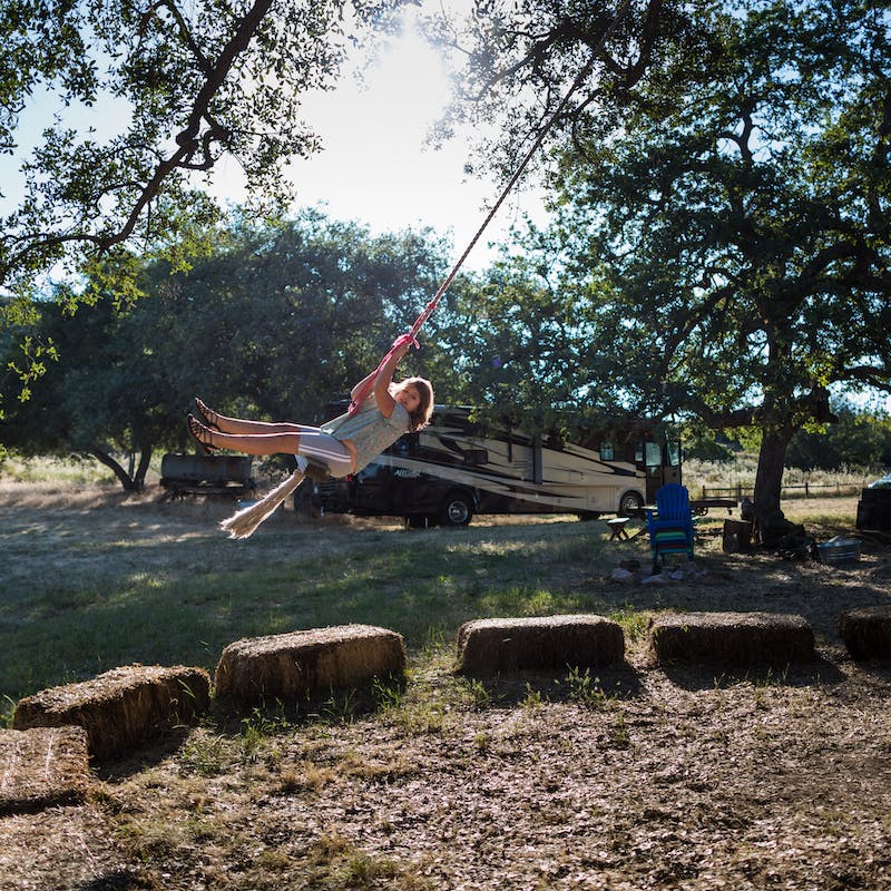 A child swings from a rope swing with an Allegro class A RV in the background.