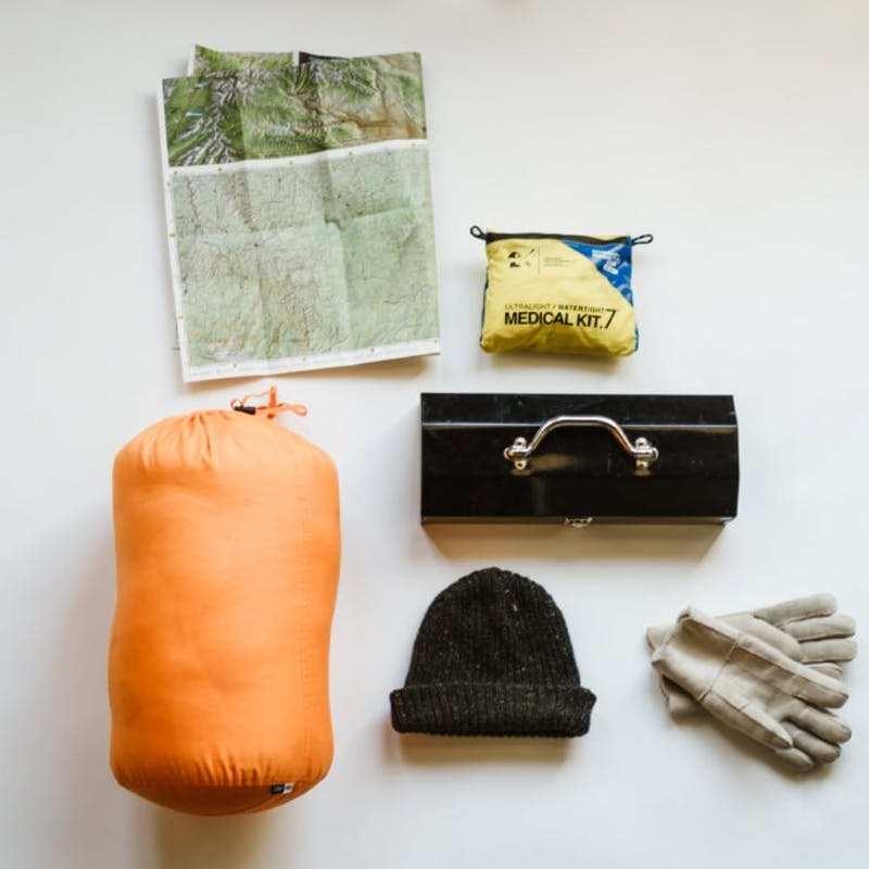 Camping gear laid out including a sleeping bag, map, gloves, medical kit, hat, and toolbox