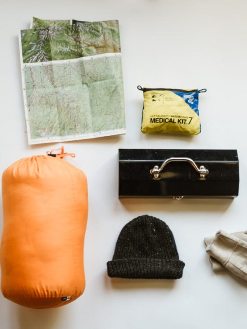 Camping items laid out on white background, including sleeping bag, map, medical kit, hat, tool box, and gloves