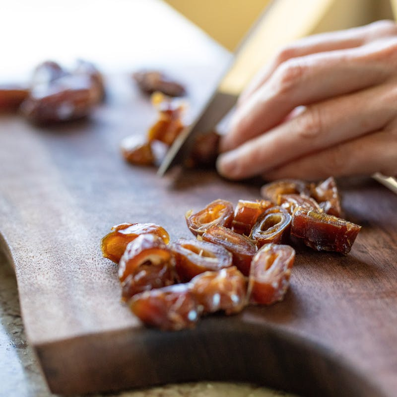 Close up of hands slicing dried dates with a knife on a cutting board.