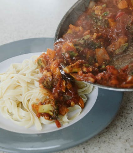 A hand pouring a veggie-filled tomato sauce from a pan onto noodles.