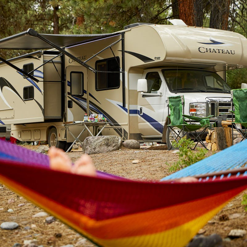 A participants relaxes in a rainbow hammock in front of a Thor Motor Coach Class C RV.
