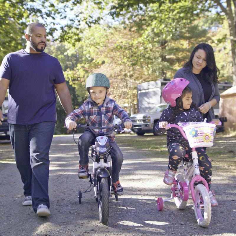 Luis and Sandra walking alongside their kids riding bikes through an RV campground.