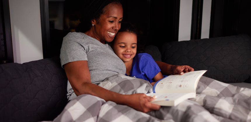 Robin reads a book to her granddaughter in one of the bunkbeds in their Keystone Fuzion toy hauler.