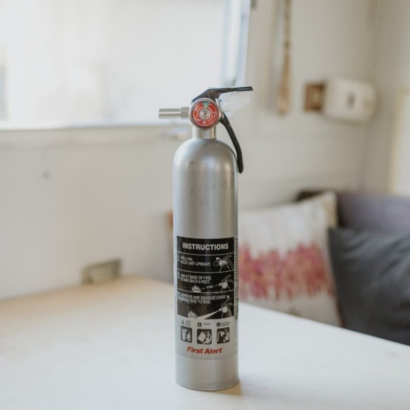 Silver fire extinguisher sitting on white table