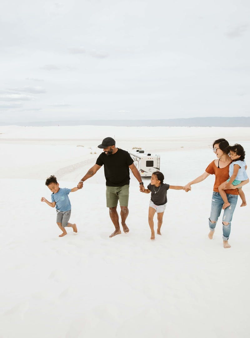 Family of five, holding hands, carry child, as they walk through white sand.